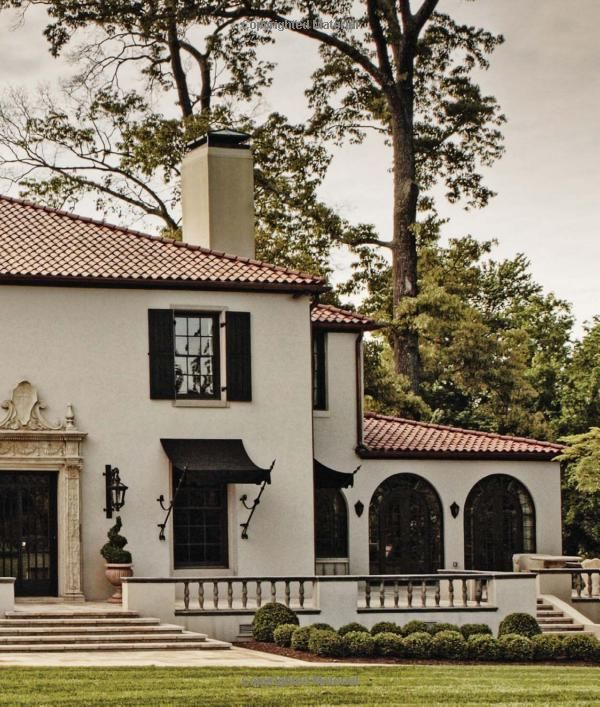 Attractive Spanish Colonial Revival Exterior Featuring White Stucco, Black Shutters  And Awnings.