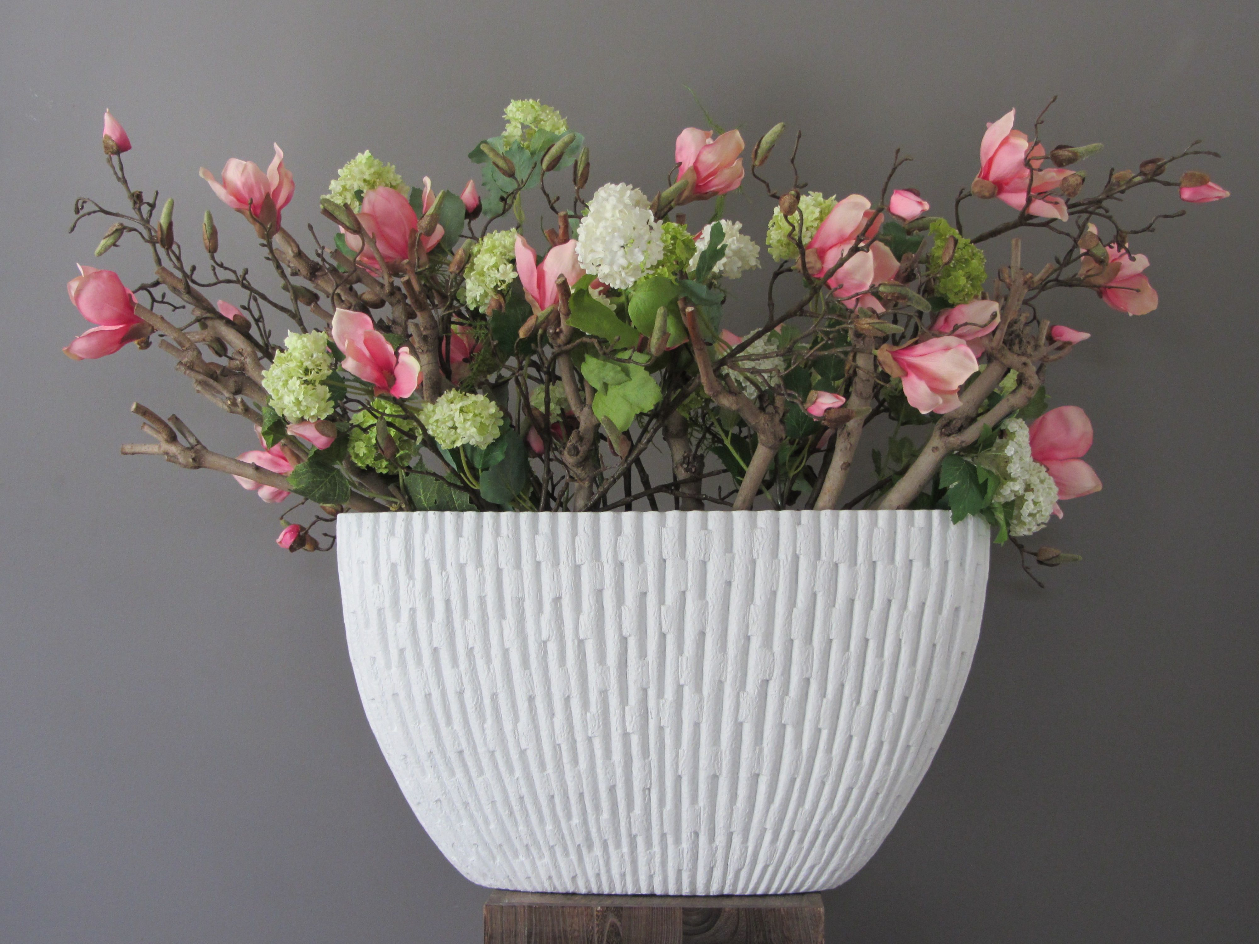 Een XL boot vaas gevuld met lange zijden lichtroze magnolia takken, zijden sneeuwballen en veel seringenhout. www.abonneefleur.nl