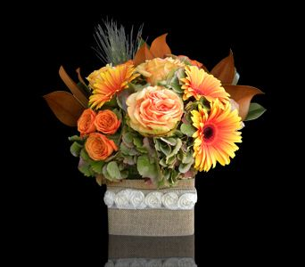 Rustic Elegance - Rustic green hydrangea, roses, gerbera daisies, magnolia leaves and sprigs of wheat arranged in a vase bound in burlap adorned with a rosette ribbon.