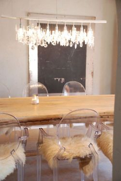 Lucite chairs with fur rugs and wood slab dining table.