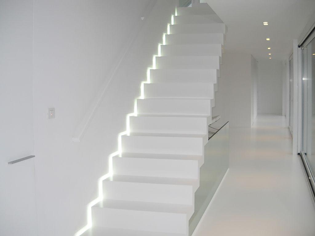 Moderne witte trap van Corian met ingebouwde ledverlichting langs de ...