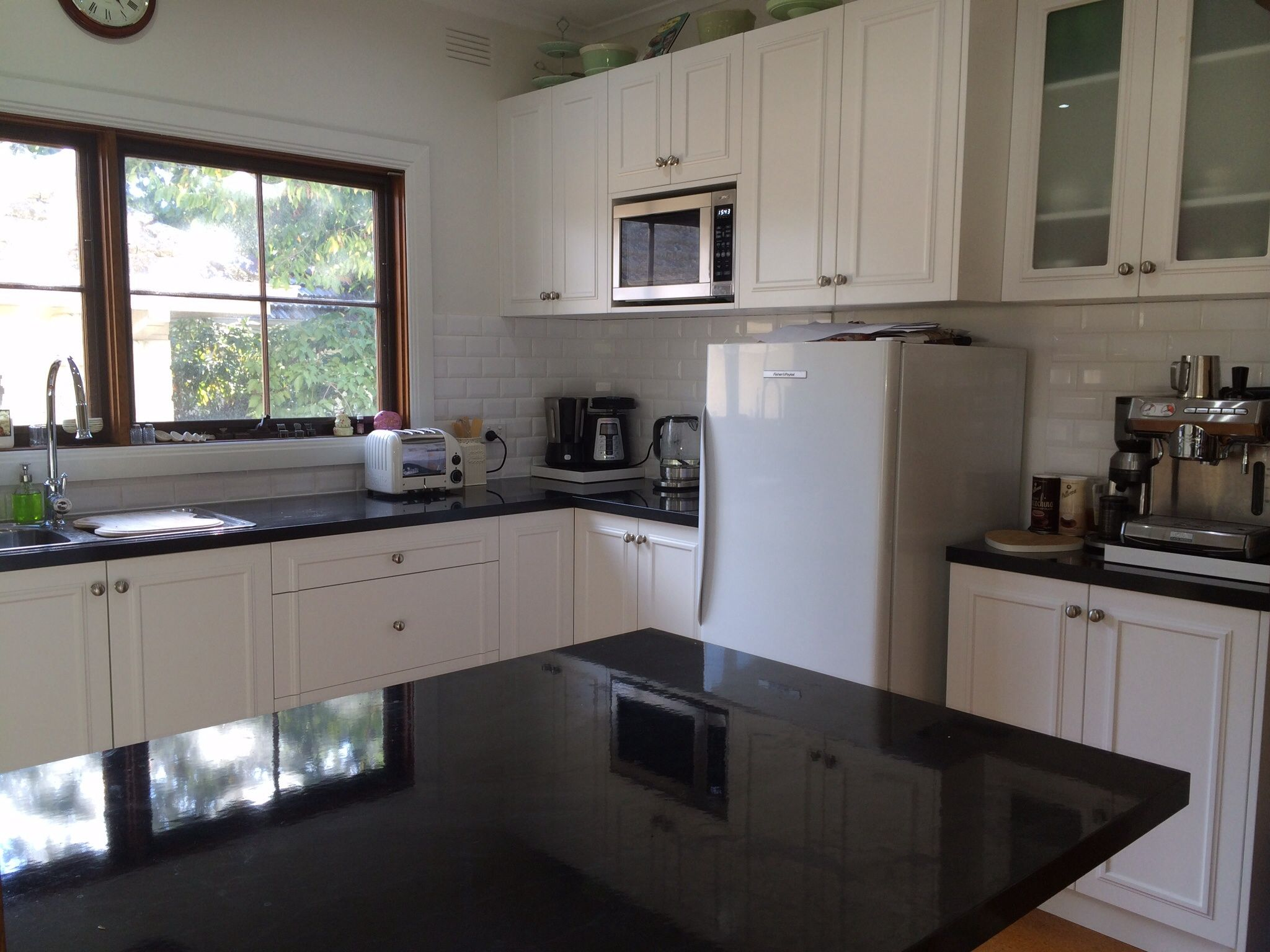 White Kitchen Black Benchtop finished result with white subway tile splash back, black benchtop