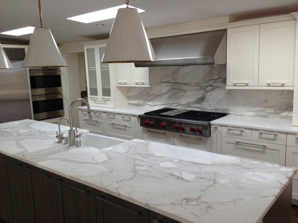 A remodeled kitchen with a slab of granite island matching for Granite countertop design ideas