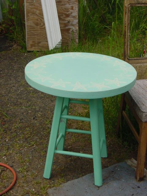 Old stool and cut round piece of wood...add some paint....now its a table!