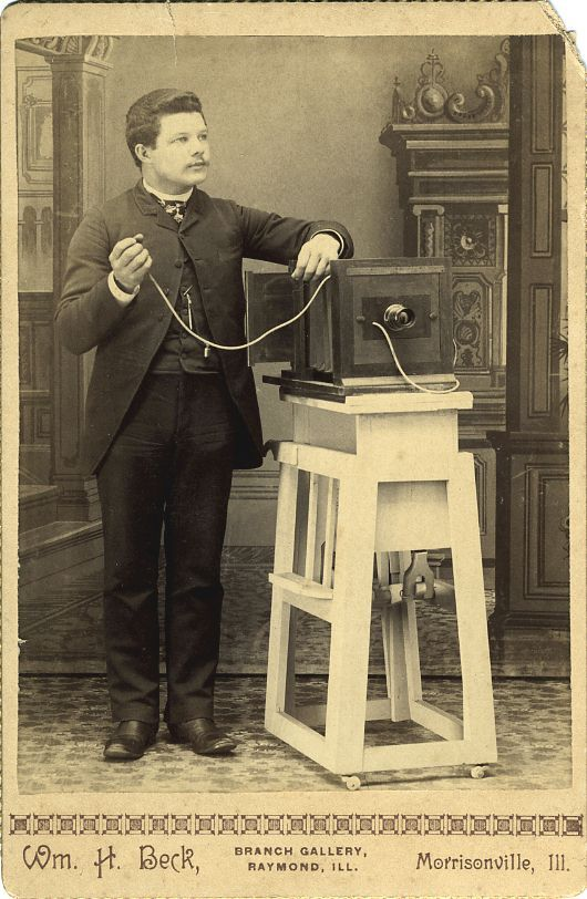 "PHOTOGRAPHER WITH CAMERA. Cabinet card, 61/2"" x 4 1/4"". View of William Beck (or assistant) with camera on tripod. Wm. Beck, Morrisville, Ill"