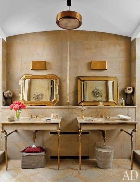 Stefano Pilati's Paris Duplex Apartment Renovation | Honey-color stone lines the master bath. A narwhal tusk bought at Christie's is displayed on the shelf above the sinks, which feature Lefroy Brooks fittings.