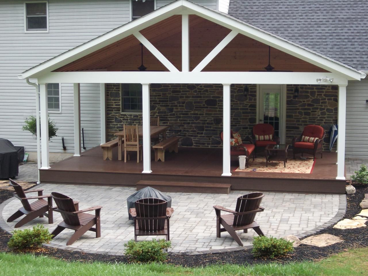 A Frame Roof With Exposed Cedar Framing, Stone Backdrop, And Vinyl Covered  Posts