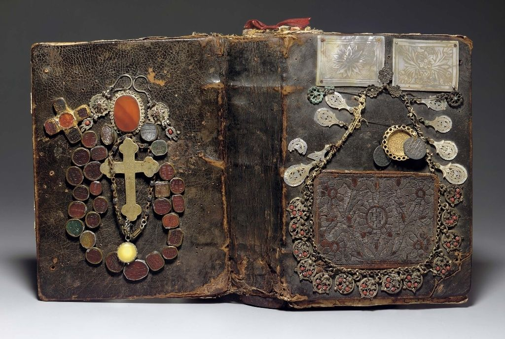An unusual type of metal decoration found on a number of Armenian manuscript bindings. These bindings were embellished with odd objects haphazardly attached onto the covers, and sometimes even onto the spine and flap. The items may include coins, crosses, crucifixes, seal stones from personal signet rings, metal belts, jewelry, and small metal repousse objects shaped liked hands, eyes, crescent moons, or human faces.