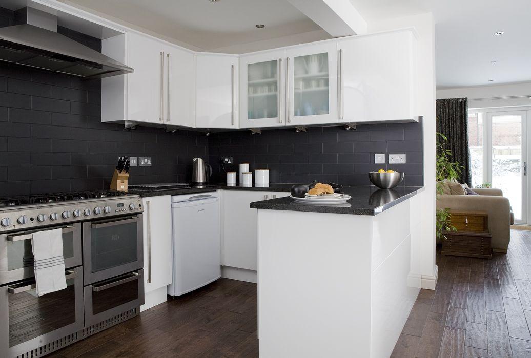 White gloss kitchen, walnut flooring and black matt metro tiles.