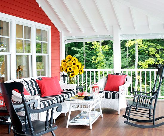 Wicker furniture and rocking chairs are porch classics. Keep a traditional grouping lively with contrast: white wicker, dark rockers, and stylish fabric choices. Black-and-white-striped cushions and bright red accent pillows give a decidedly modern feel to the traditional pieces.