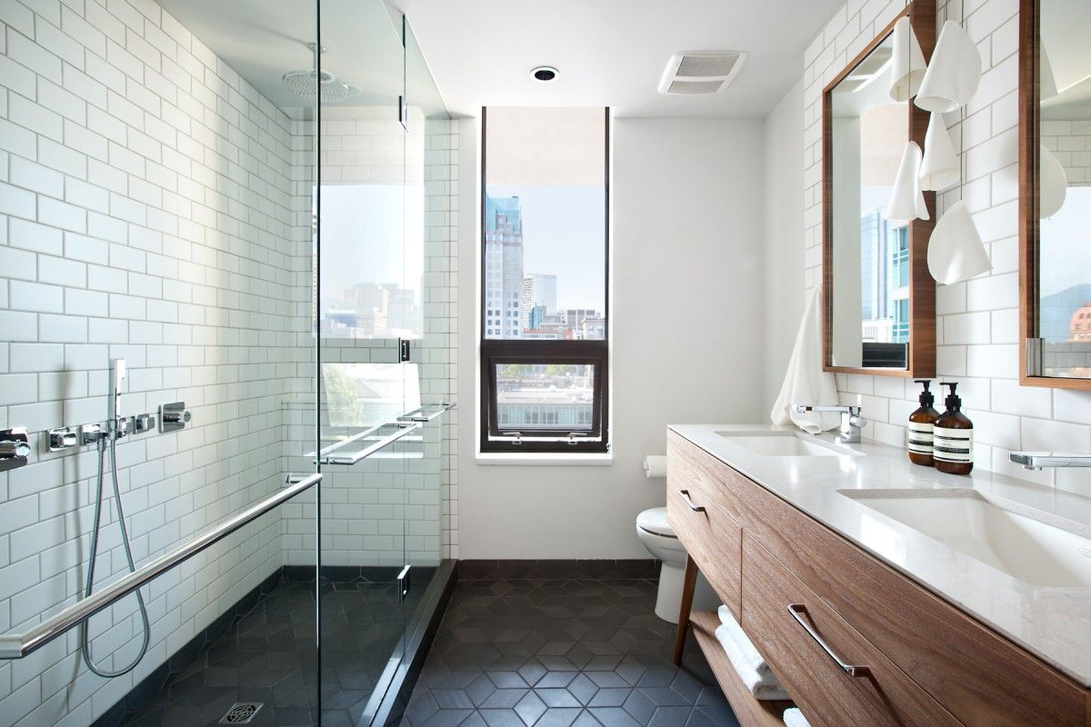 Interior Design by Falken Reynolds - Vancouver loft ensuite bathroom with American Mid Century Modern inspired walnut double vanity, Caesarstone counters, framed recessed medicine cabinets, white subway tile walls, Mutina Ceramics black Tex hexagon tile floors, Bocci21pendant, photo by Ema Peter