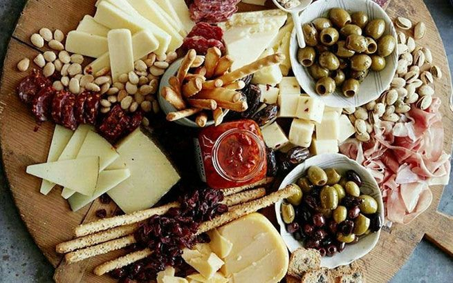 Käseplatte mediterran dekoriert mit Oliven und Grissini