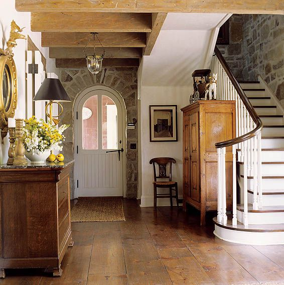 What is not to love about this space...wide plank floors, arched door, curved stair rails, the stone work...