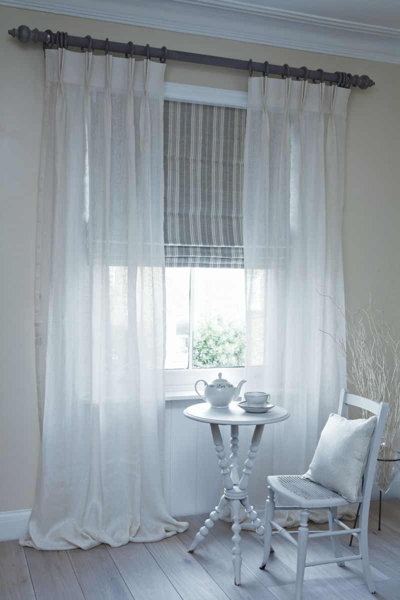 Neutral blinds and sheer curtains gives the room a soft bright