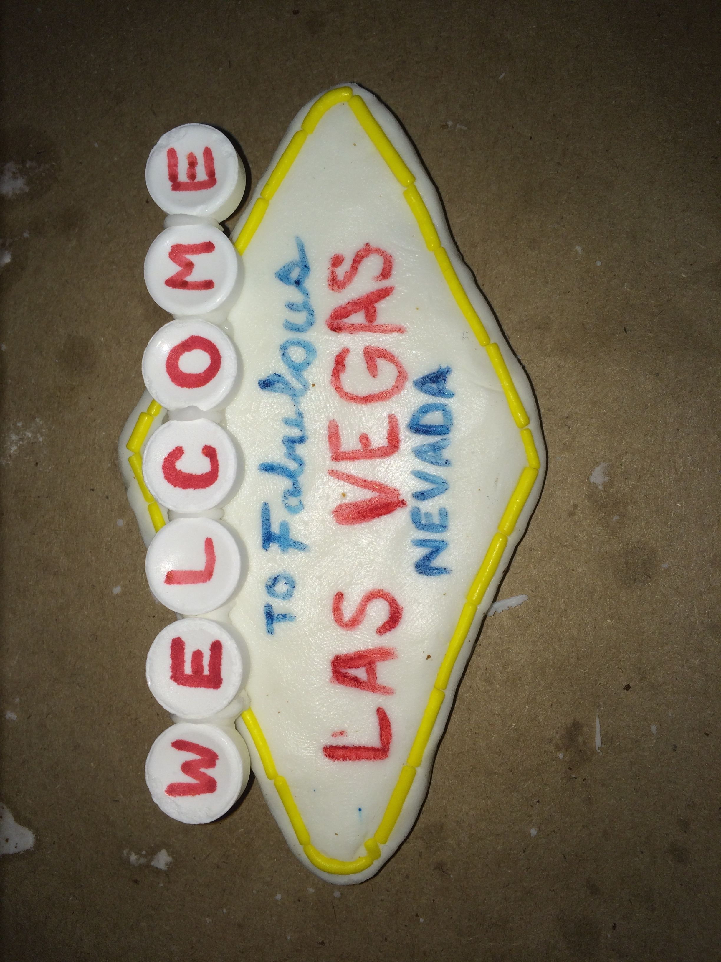 Beginnings of the Fabulous Las Vegas sign. Welcome done on Smarties. Back of sign is gingerbread. White is modeling chocolate (writing with edible marker). Yellow edge done in sprinkles.