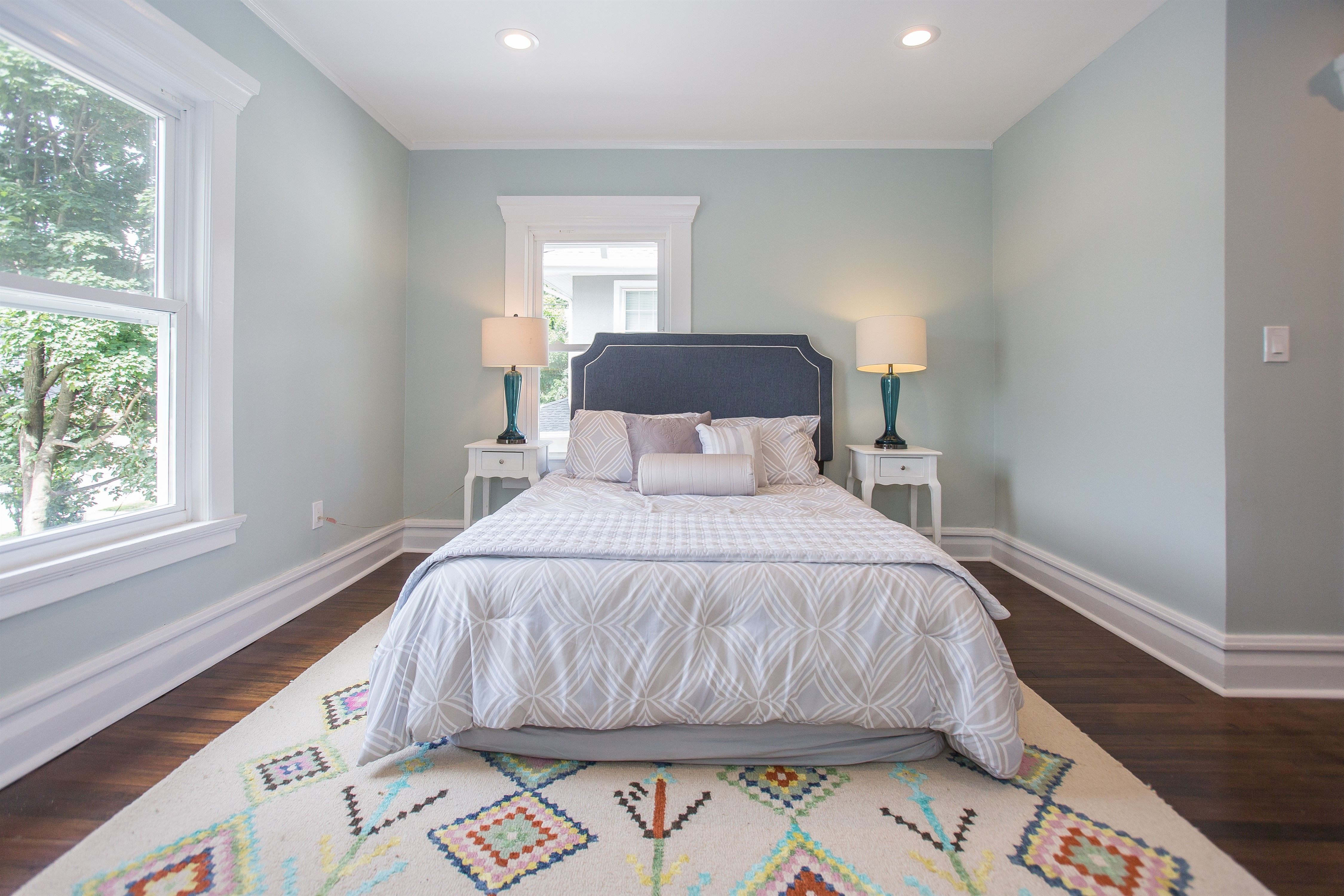 Spacious master bedroom with recessed lighting and natural