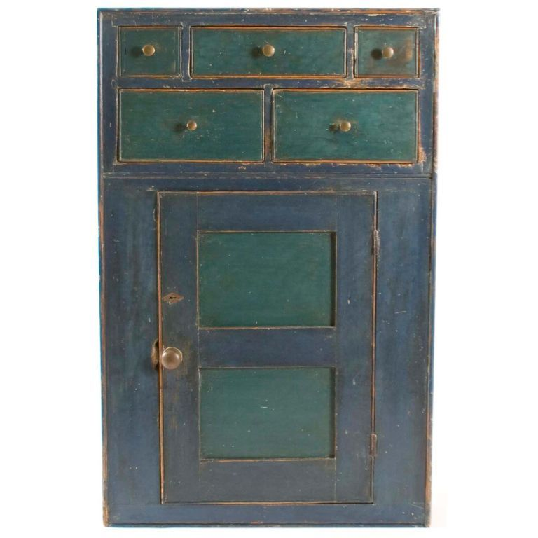 This hanging cupboard has a three-over two-drawer arrangement over a paneled door with original escutcheon and pulls. The cupboard is painted an old dark-blue paint with green painted drawers. It has three sunken panels on each of the sides. LENGTH: 18.75 in. (48 cm) DEPTH: 8.5 in. (22 cm) HEIGHT: 29 in. (74 cm) Chester, PA