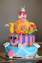 a lovely and creative Alice In Wonderland birthday cake with many colorful layers and accents