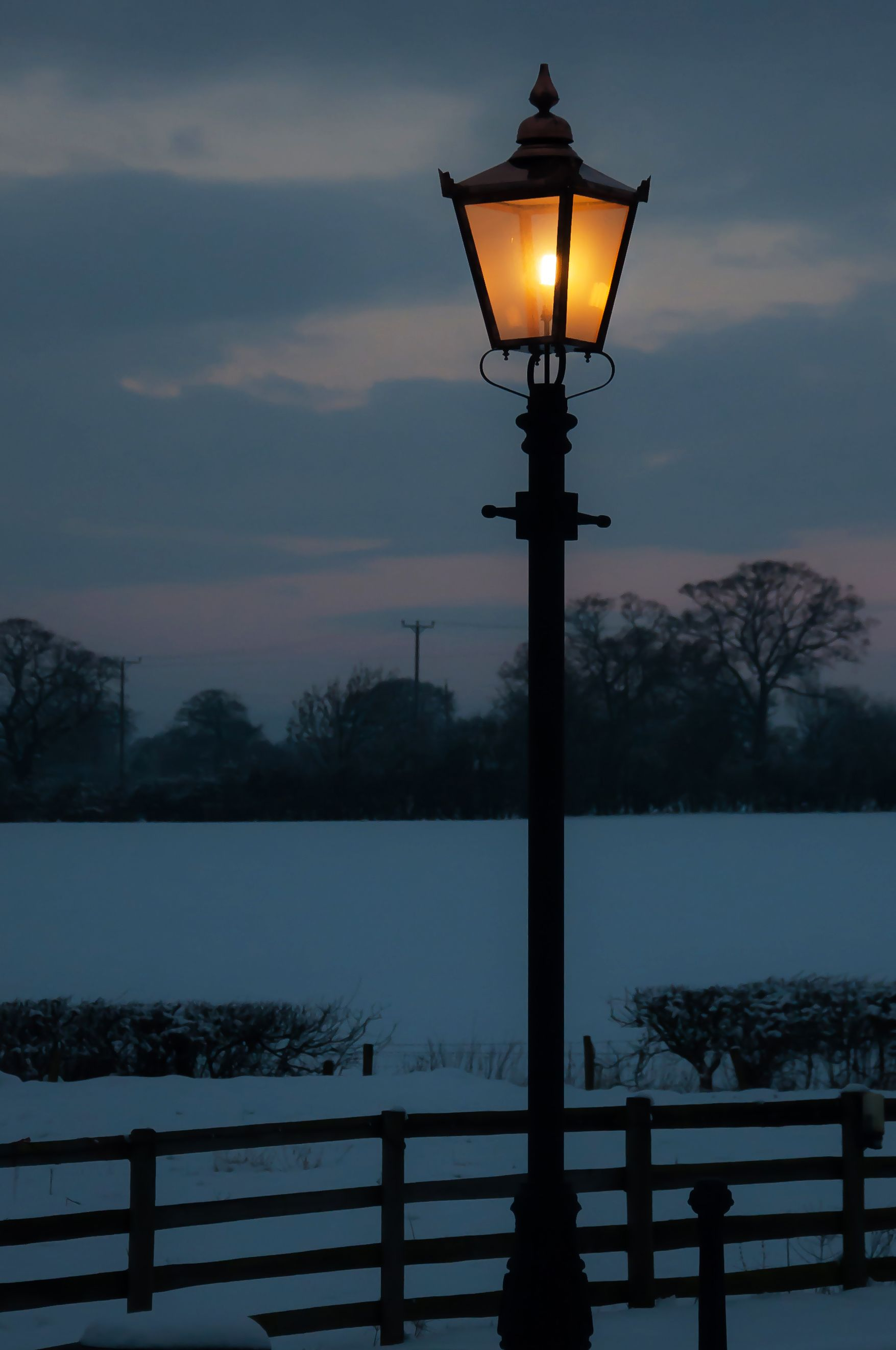 A traditional Victorian lamp post glowing on a winters evening.