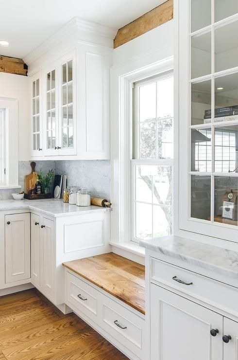 A mix of warm and light hues bring a white farmhouse kitchen together beautifull...