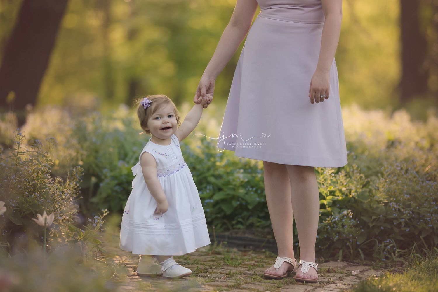 1 year old little girl holds mother's hand while standing