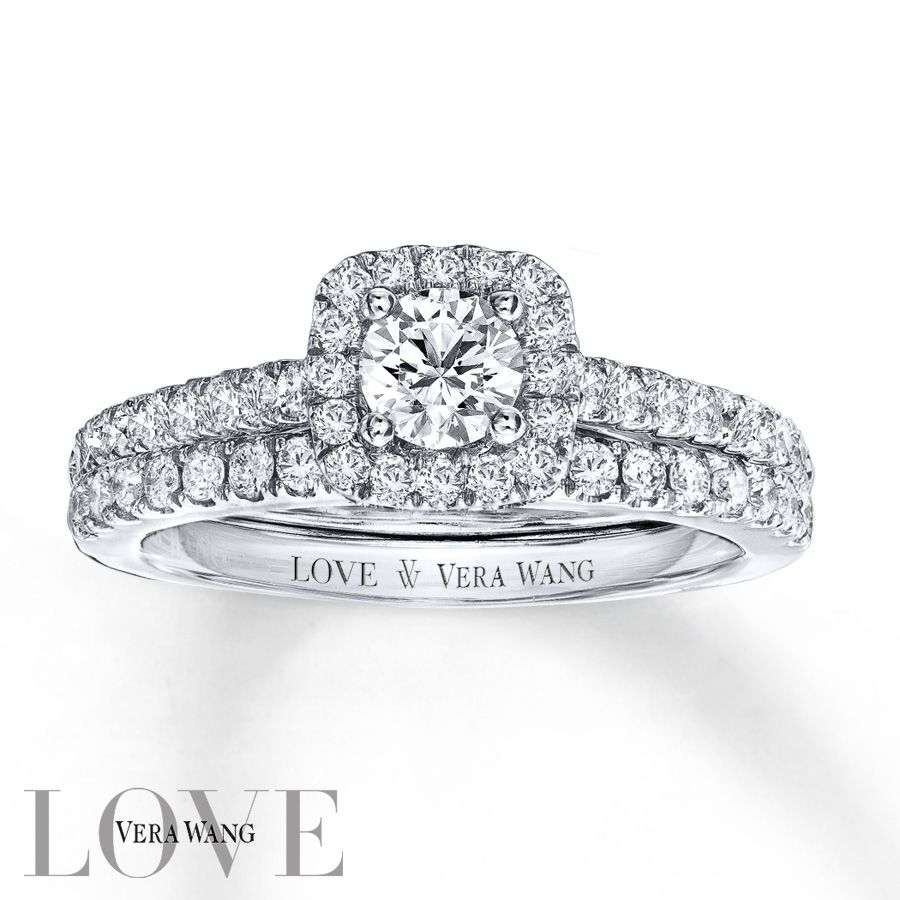 From the Vera Wang LOVE Collection, this captivating engagement ring features a mesmerizing 1/3 carat round center diamond surrounded by a frame of smaller accent diamonds. Additional diamonds grace the ring's band on all sides, ensuring sparkle from every angle. Set into the bezel are two princess-cut sapphires, the signature of the collection and a symbol of faithfulness and everlasting love. The coordinating wedding band features an additional row of shimmering diamonds to complete the…