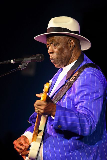 "George ""Buddy"" Guy (Born July 30, 1936) Guy is a five-time Grammy Award-winning American Blues Guitarist and Singer. He is well known for playing his guitar with drumsticks, or strolling into the audience while trailing a long guitar cord with him. http://voices.yahoo.com/top-10-blues-singers-all-time-3392498.html"