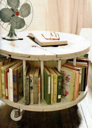 Wooden spool made into coffee table/bookshelf on casters.