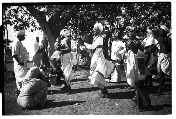 Itinerant minstrels halt at some place under banyan tree.Crowd gathers,news of WW II told with song & dance