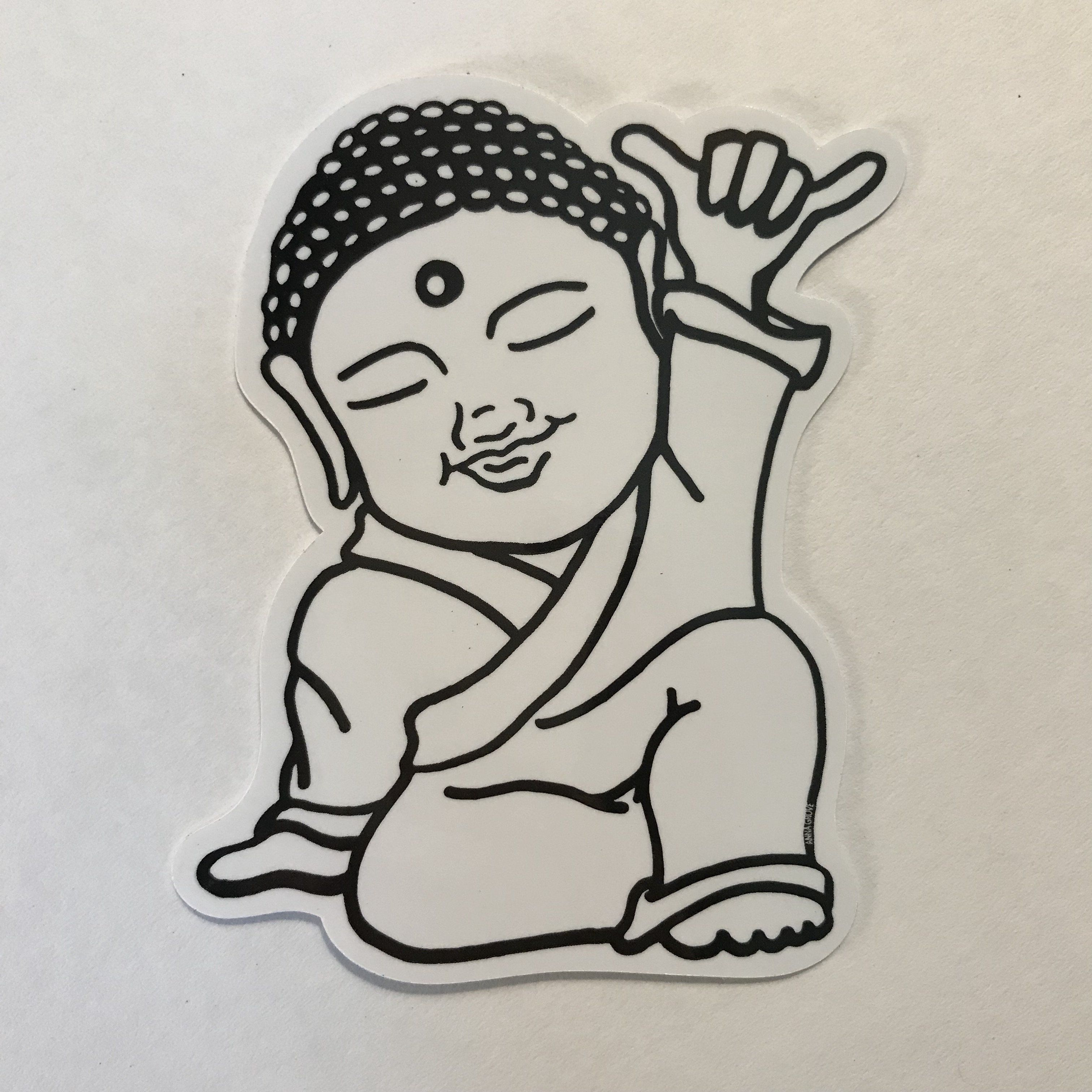 "This custom Shaka Buddha die cut vinyl sticker is great to put anywhere. Will adhere to car windows, surfboards, skateboards or even your water bottle. Ink will not bleed if it gets wet. Matte finish 3""x4"" in size Made with Aloha"