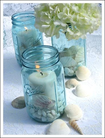 Candles in blue mason jars with a small flower in a mason jar. But maybe not mason jars. All be square vases.