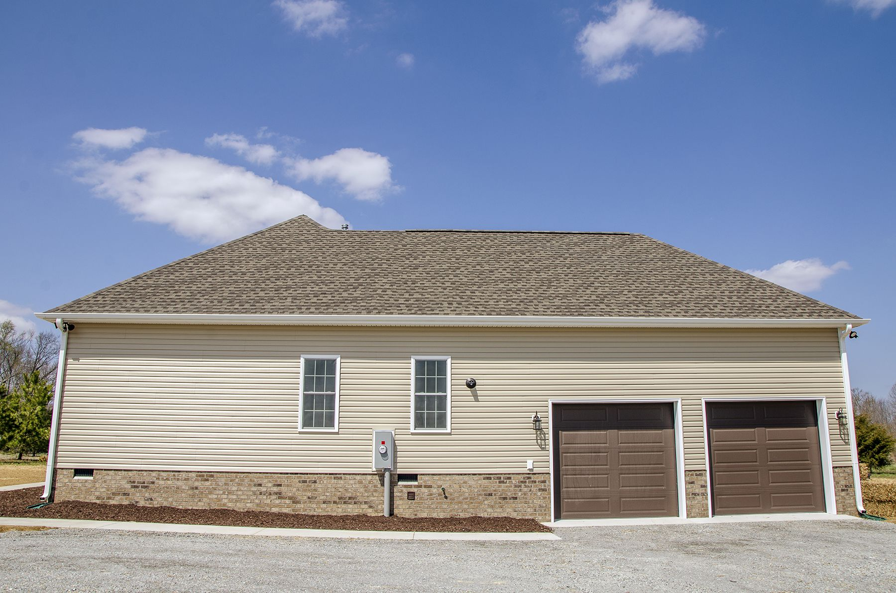 Carriage garage doors without windows  Side view of this home with an attached two car garage and brown
