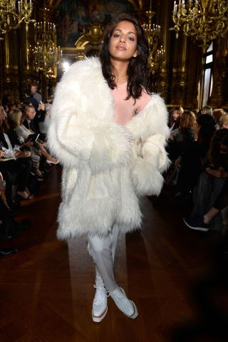 M.I.A. brings out the fur at Stella McCartney front row. See all the most stylish celebs at Paris Fashion Week: