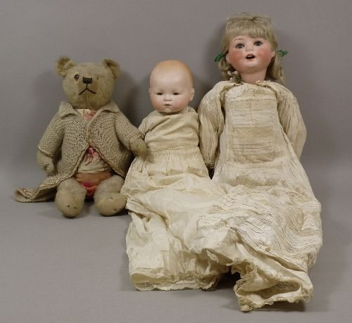 An Armand Marseille bisque headed baby doll with closing eyes and cloth body, 13ins high, three other German bisque headed dolls, a 1920s English teddy bear in old gold plus, 16ins high (playworn), and a selection of children's clothing, various
