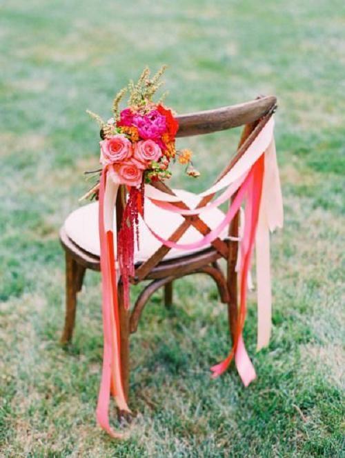 Originele stoeldecoratie met  lint en bloemen.