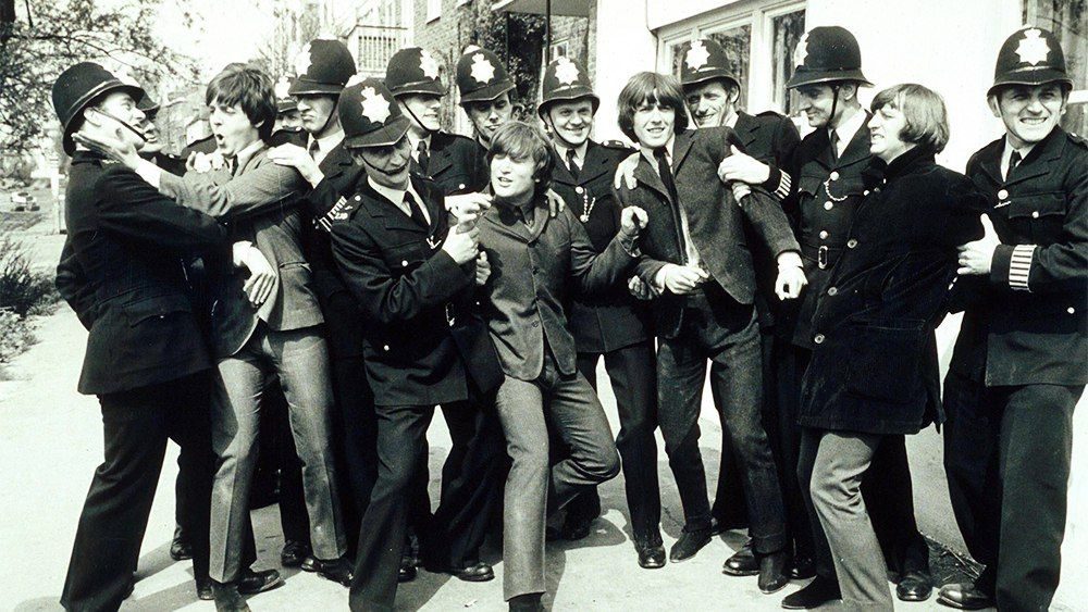 The Beatles clash with police in scenes from Help whilst filming in Chiswick 1964.