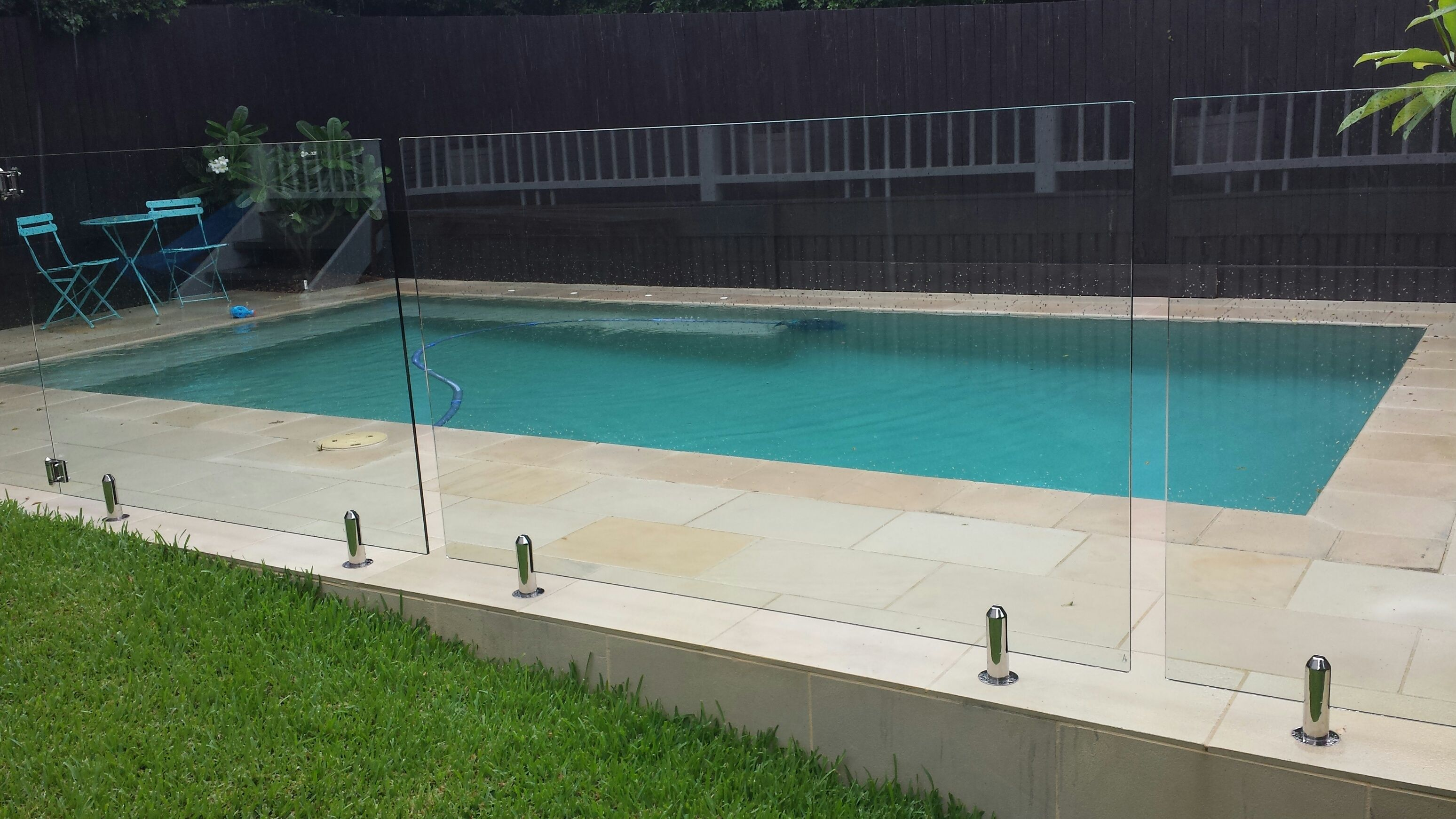 Sawn and sandblasted sandstone paving and coping around for Glass pool fences