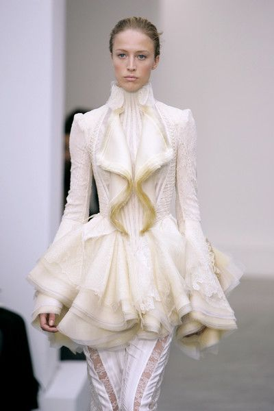 Balenciaga Spring 2006 18th century inspired 1730s. Ditto Suit. Ruffles around neck. Suits in this time period were trimmed with embroidery and lace. Sleeves ended in large full attached cuffs.