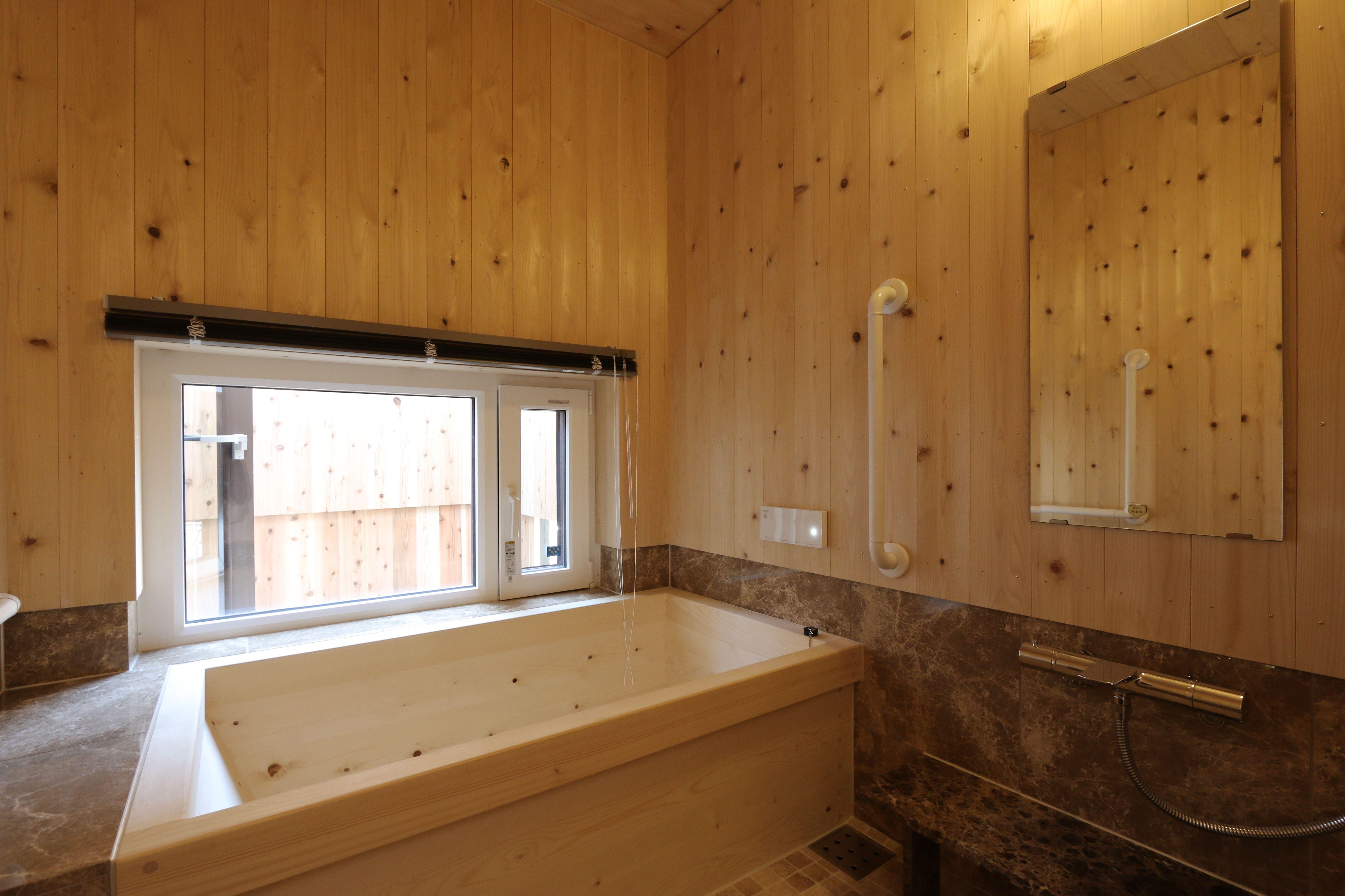 高野槇の木製の浴槽の在来浴室 壁にはブラウンの大理石と能登ヒバを使用 木製浴槽 浴室 壁 浴槽
