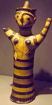 A cylindrical female figurined with upraised arms. The bell-shaped skirts and upraised arms are also seen form this period on Crete, but with stylistic differences, including the paint on the mainland icons.