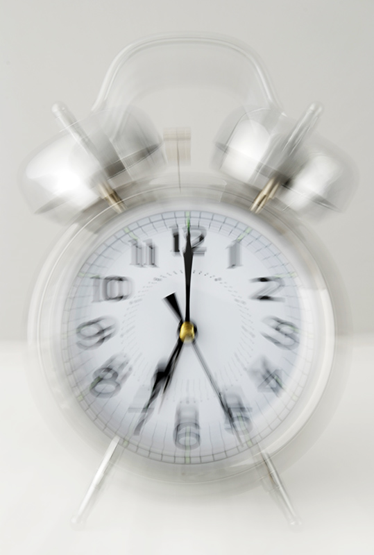 Old fashioned chrome ringing alarm clock with motion blur to give the illusion of ringing