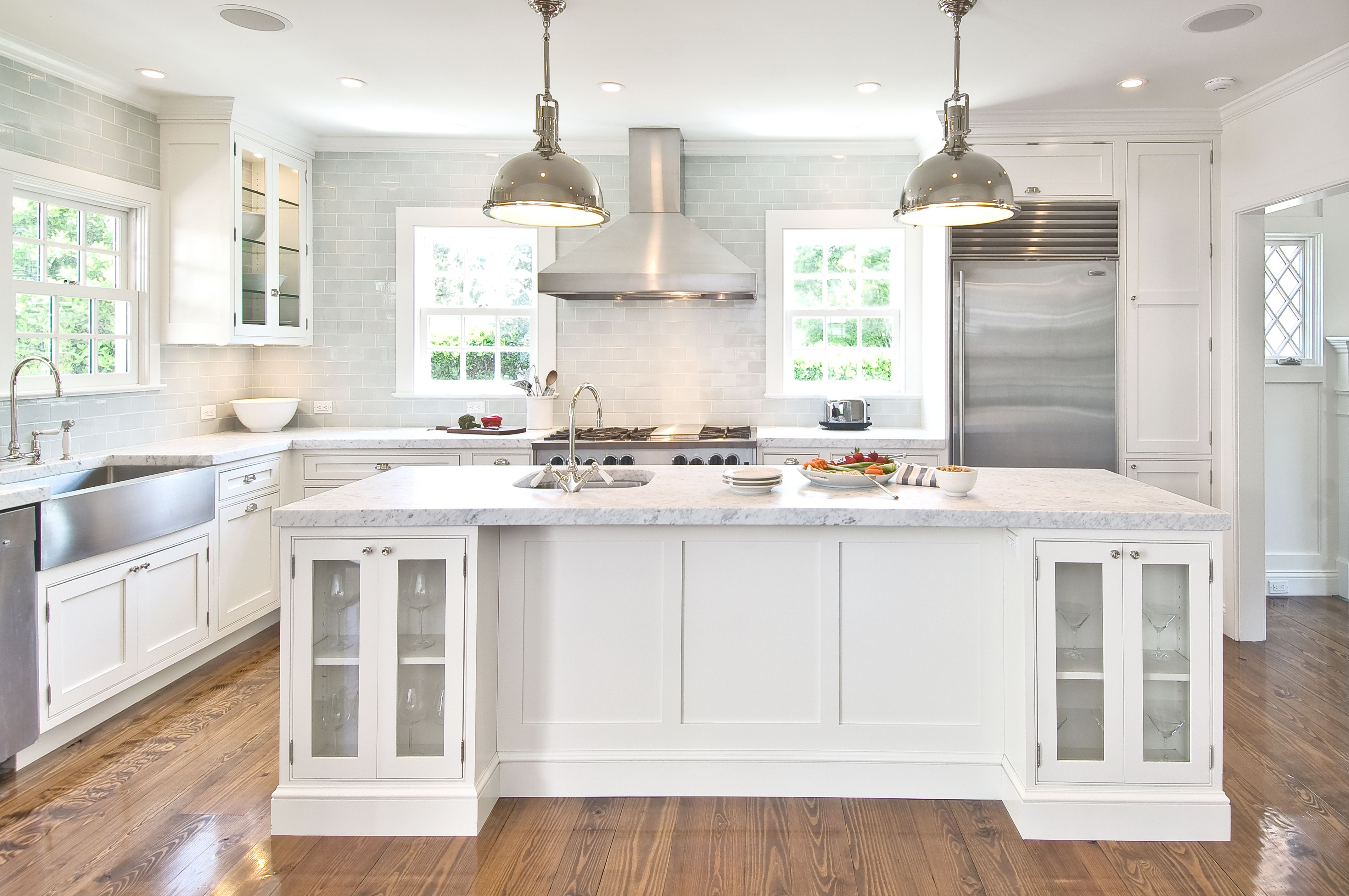 Kitchens  shaped blue subway tiles backsplash stainless steel apron sink white glass front kitchen cabinets marble countertops in island also this clean yet traditional is the quintessential hamptons