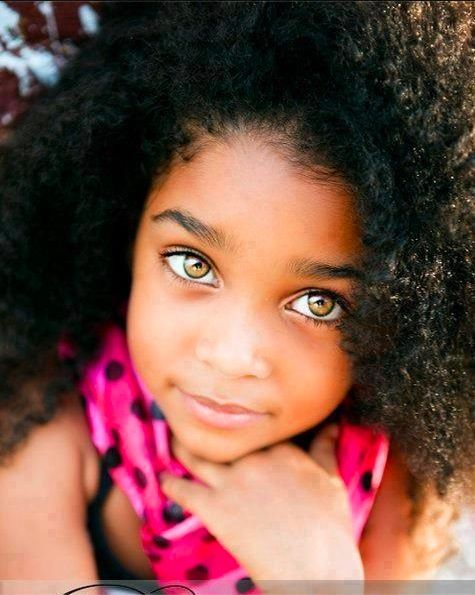 Petite fille métisse aux yeux clairs et cheveux frisés