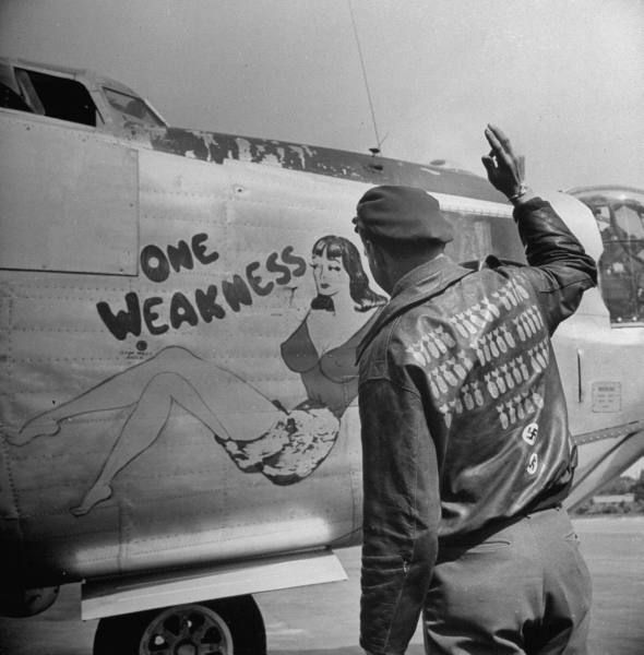 Pilot standing in front of his bomber plane named ' ONE WEAKNESS'