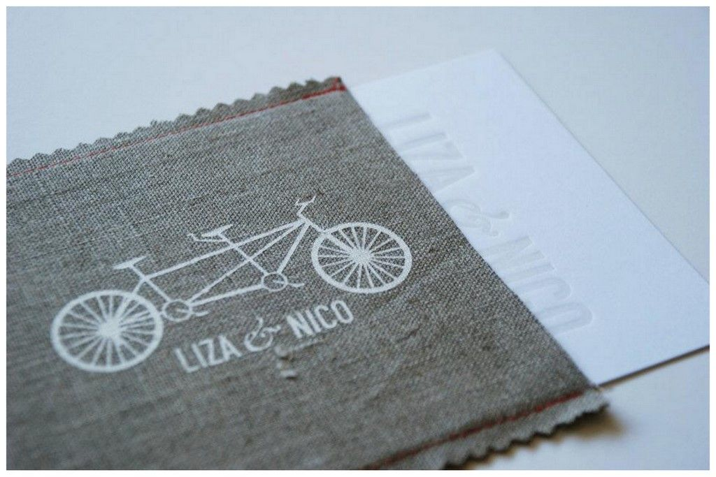 Une enveloppe en tissu pour les faire-parts. Un coup de ciseaux cranteurs, 3 coutures droites, un tampon et un peu de peinture blanche : ça doit être faisable soi-même, non ?