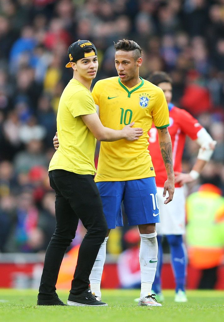 A Brazil fan runs onto the pitch to greet Neymar of Brazil during the international friendly match between Brazil and Chile at the Emirates Stadium on March 29, 2015 in London, England.