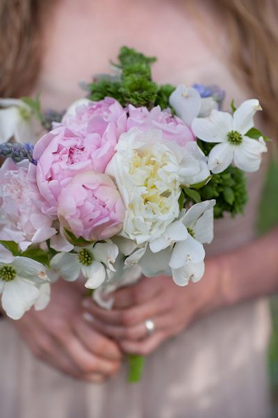 A textured bouquet with dogwood blooms, peonies, fiddle head ferns, french ranunculus, scilla, and some bluebells.