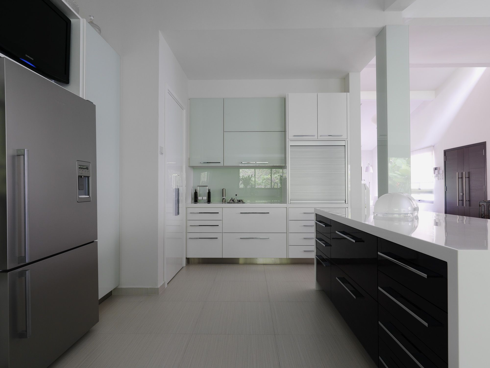 the white lacquered high gloss kitchen cabinets look complete with complimenting silver colored roller shutters