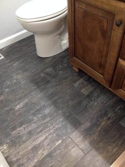 Get the rugged look of hand scraped wood with the durability of porcelain  with the Montagna Smoky Black floor
