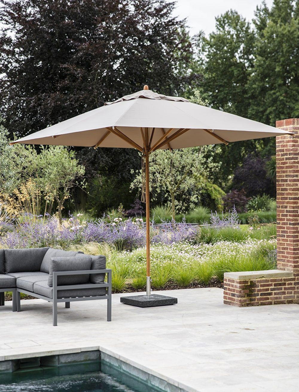 Outdoor parasol with a thick dark granite base pictured next to the west strand corner